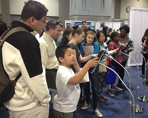 Visitors play an iPad game *Who Wants to be a Bioengineer?* (NIBIB)