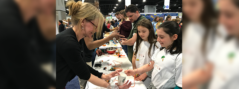 A volunteer helps children experience how their brain and spinal cord control their bodies' movements and muscle contractions. (National Institute of Mental Health)