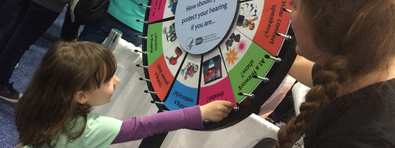 Using the Noisy Planet Q/A spinning wheel, a volunteer teaches a visitor about healthy hearing habits for common noises. (National Institute on Deafness and Other Communication Disorders)