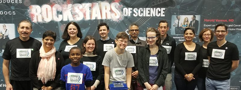 Volunteers and participants in front of the NIH Rock Stars of Science display which features NIH scientists (such as NIH Director Francis Collins and NIAID Director Anthony Fauci) alongside popular rock stars (such as Joe Perry and Sheryl Crow).