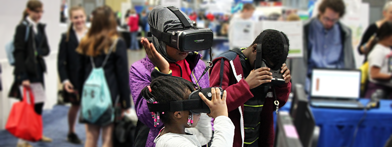 Visitors wearing virtual reality headsets to view protein structures in 3-D. (National Institute of General Medical Sciences)