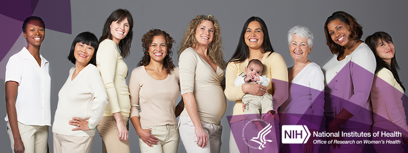 Nine women of various ages and race. One is pregnant and one is holding an infant. All are standing together and leaning on each other while smiling.